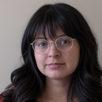 Headshot of person with brown hair, bangs, and glasses
